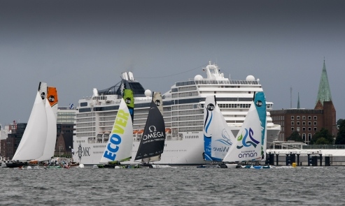 Extreme Sailing Series Fleet crosses by a cruise ship in Kiel ( Photo by Paul Wyeth / OC Events )