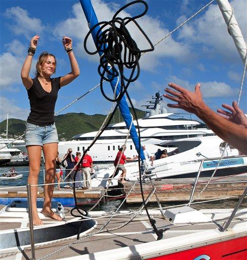 "Dutch sailor Laura Dekker throws a rope as she docks her boat in Simpson Bay Marina in St. Maarten, Saturday Jan. 21, 2012. Dekker ended a yearlong voyage aboard her sailboat named ""Guppy"" that made her the youngest person ever to sail alone around the globe, although Guinness World Records and the World Sailing Speed Record Council did not verify the voyage, saying they no longer recognize records for youngest sailors to discourage dangerous attempts. (Photo by AP Photo/Stephan Kogelman)"