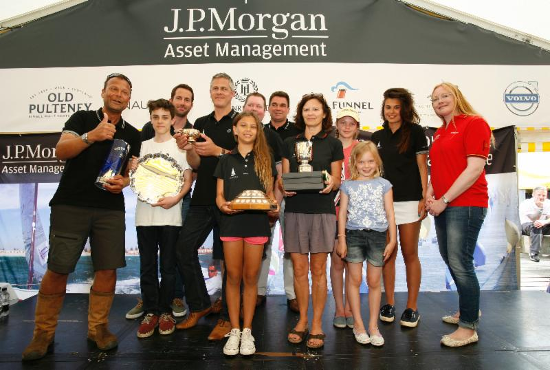 Folkboat Madelaine's skipper Edward Donald (left), crew & the family Donald celebrating winning the Gold Roman Bowl & additional trophies presented by Sir Ben Ainslie at the 2014 J.P. Morgan Asset Management Round the Island Race. (Photo by Patrick Eden)