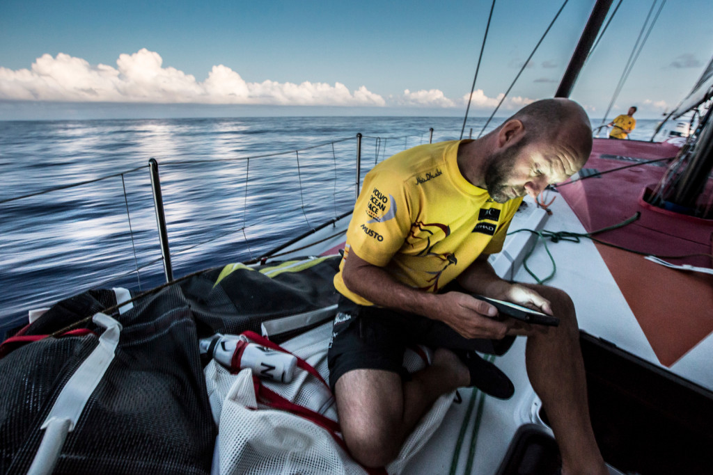 April 24, 2015. Leg 6 Newport onboard Abu Dhabi Ocean Racing. Day 5.  Ian Walker looks at the nav computer to check positioning on the rest of the fleet as a front approaches in the sky. (Photo by Matt Knighton / Abu Dhabi Ocean Racing / Volvo Ocean Race)