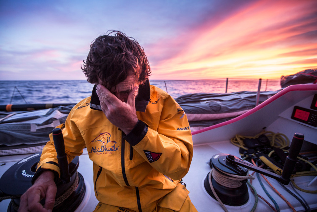 May 5, 2015. Leg 6 Newport onboard Abu Dhabi Ocean Racing. Day 16.  Roberto Bermudez 'Chuny' wipes his eyes backlit by a magnificent sunset over the Atlantic Ocean.  (Photo by Matt Knighton / Abu Dhabi Ocean Racing / Volvo Ocean Race)